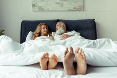 Feet of happy mature couple resting together in bed Stock Photography