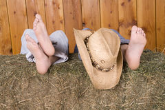 Feet and hat on hay. Human feet sitting on top of a hay bale with a hat laying on their feet Royalty Free Stock Photo