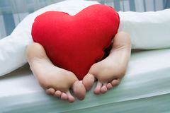 Feet with heart. Image of bare feet with red soft heartshaped pillow Royalty Free Stock Photography