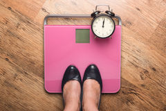 The feet in high heels standing on bathroom scales Royalty Free Stock Images