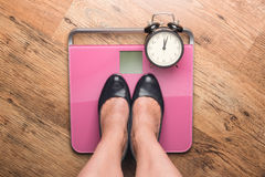 The feet in high heels standing on bathroom scales Stock Image
