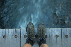 Feet on a wood bridge with flowing water down below Royalty Free Stock Photo
