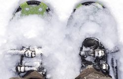 Feet with hiking snowshoes covered in snow. Cold weather Stock Photos