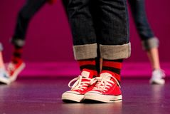 Feet of a hip-hop performer in red sneakers. With more dancers in the background Royalty Free Stock Photography