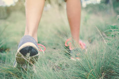 Feet of hipster girl walking in forest background. Relax time on holiday Stock Photos