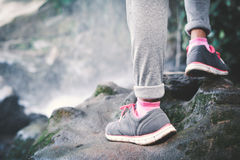 Feet of hipster girl walking in waterfall background. Relax time on holiday stock image