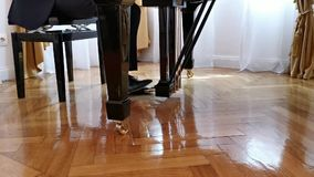 Feet hit the piano pedals. Legs of a pianist man while playing piano stock video footage