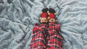 Feet at home in bed dressed socks with cute teddy bears and in pajamas. top of view. Playing foot at home in bed dressed socks with teddy bears and in pajamas Stock Image