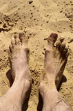 Feet on the hot sand Stock Images