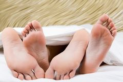 Feet hug. Image of two pairs of bare male and female feet during sleep Stock Image