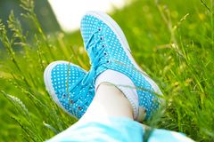 Feet In Sneakers On Green Grass Royalty Free Stock Image