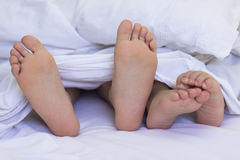 Feet In The Bed Sheets Royalty Free Stock Photos
