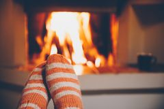 Free Feet In Wool Striped Socks By The Fireplace. Relaxing At Christmas Fireplace On Holiday Evening Royalty Free Stock Images - 160908569