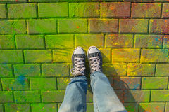 Feet in jaeans sneaker top view on the holi background.. Royalty Free Stock Photography