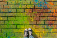 Feet in jaeans sneaker top view on the holi background.. Stock Image