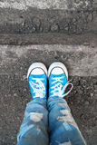 Feet in jeans and blue shoes stand on street edge Royalty Free Stock Photography