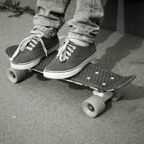 Feet in jeans and gumshoes on a skateboard Stock Images