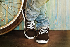 Feet in jeans and sneakers. Alongside a bicycle Royalty Free Stock Images