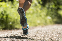Feet of a jogger. Running in a trail path Stock Photo