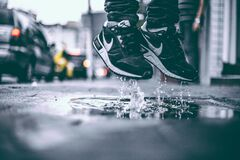 Feet jumping in puddle Stock Photos