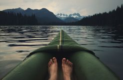 Feet in kayak on alpine lake Royalty Free Stock Photo