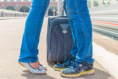 Feet kissing couple near a suitcase Stock Photos