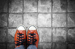 Feet in leather sneaker on pavement background Stock Photos