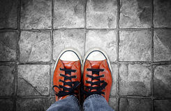 Feet in leather sneaker on pavement background Royalty Free Stock Photos