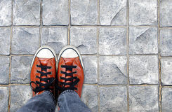 Feet in leather sneaker on pavement background. Top view Stock Photography