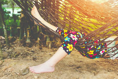 Feet and legs of child enjoying and relaxing in hammock royalty free stock photo