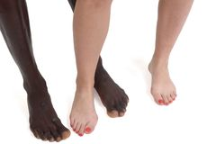 Feet and legs of an interracial couple. On white Stock Photos