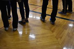 Feet and legs of people waiting in a school gym royalty free stock image