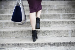 Feet and legs of woman walking up steps. Woman walking up stone steps symbolising career progression and progress Royalty Free Stock Photo