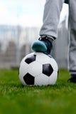 Feet of little boy on ball on football field Stock Photos