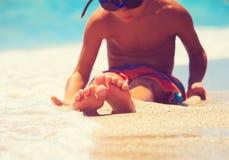 Feet of little boy relax at summer beach. Feet of little boy relax at summer sand beach Stock Photo