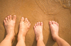 Feet of little boy standing alone on the sand. Beach Stock Image
