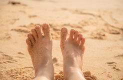 Feet of little boy standing alone on the sand Stock Photos