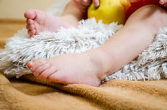 Feet of a little girl on a beige background Royalty Free Stock Image