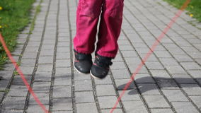 Feet of little girl jumping rope stock video footage