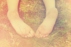 Feet of little girl outdoors Stock Photos