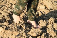 Feet of kid - girl walking on field. Feet of little kid - barefoot girl walking on ground of dried field royalty free stock photos