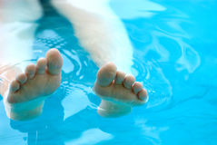 Feet lounging in a pool. With space on the right for type stock image