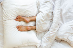 Feet lying on soft white pillow at bed. Closeup view of feet lying on soft white pillow at bed Royalty Free Stock Photo