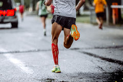 Feet male athlete taping on calf muscles. Running city marathon Stock Photos