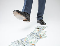 Feet of man in black shoes going by money track Royalty Free Stock Photography