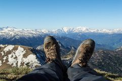 The feet of a man in boots against the background of snow-capped mountains after climbing to the top on a sunny spring morning royalty free stock image