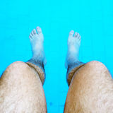 Feet in. Man dipping his feet in a pool during summertime on vacation Royalty Free Stock Photos