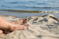 The feet of man lie on sand Royalty Free Stock Photo