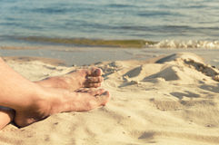 Feet of man lie on sand Stock Photography
