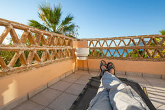 Feet of man relaxing on sun lounger Stock Image